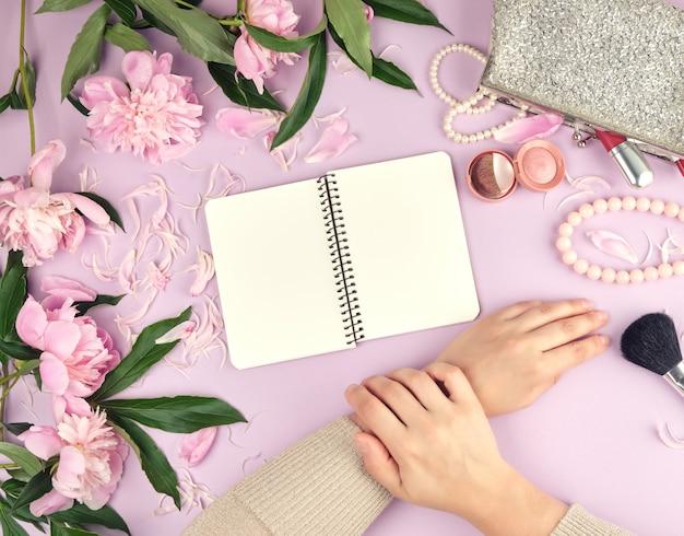 Deux mains avec la peau lisse d'une jeune fille et un sac à main avec des produits cosmétiques, bouquet de pivoines roses en fleurs Photo Premium