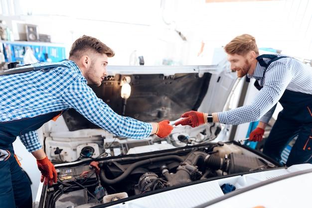 Deux mécaniciens automobiles cherchent sous le capot. Photo Premium