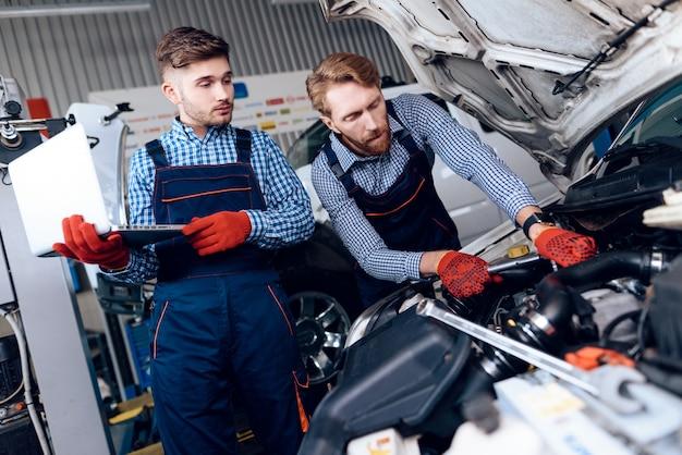 Deux mécaniciens automobiles travaillent dans un garage sur une machine cassée. Photo Premium