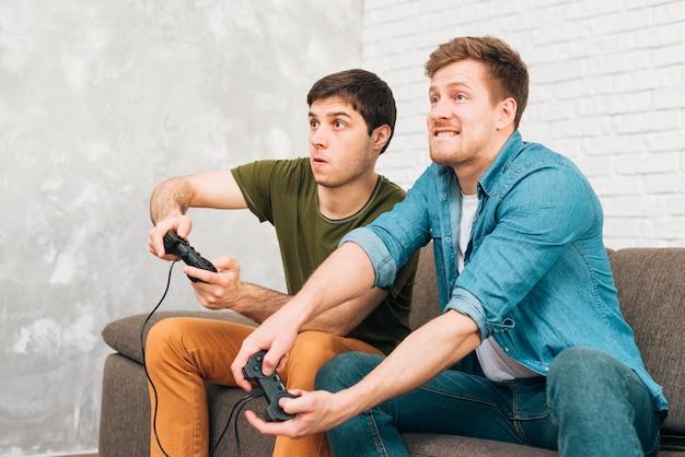 Deux mecs jouant sur la console assis sur le canapé Photo gratuit