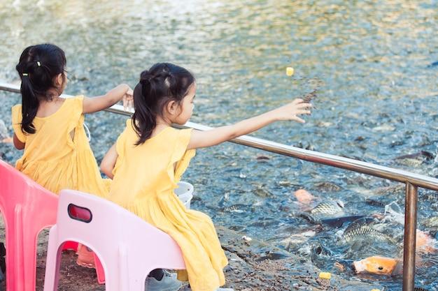 Deux Mignonnes Petites Filles Asiatiques S'amuser à Nourrir Et Donner De La Nourriture Pour Pêcher Dans L'étang Ensemble Photo Premium