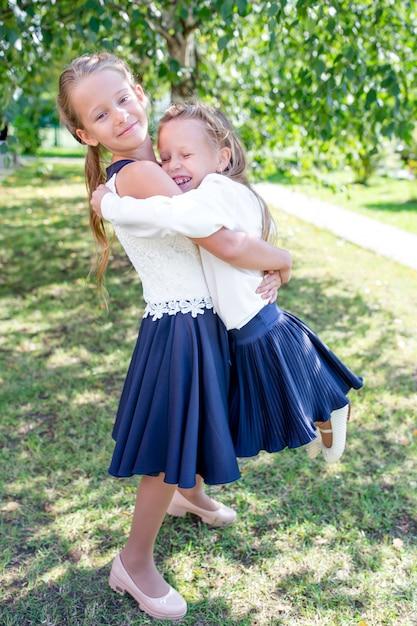 Deux mignonnes petites filles souriantes posant devant leur école. Photo Premium