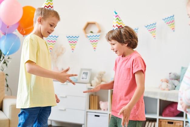 Deux Mignons Petits Garçons En Casquettes Et T-shirts D'anniversaire Jouant à Un Jeu Enfantin à La Maison Dans Une Salle Décorée à La Fête Photo Premium