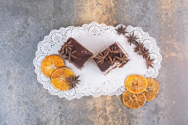 Deux Morceaux De Gâteaux à L'orange Séchée Et Anis étoiles Sur Une Surface Blanche Photo gratuit