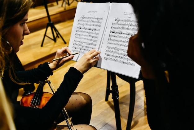 Deux musiciennes corrigeant une partition avec un crayon avant que l'orchestre ne commence à jouer. Photo Premium
