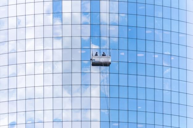 Deux nettoyants lavant les fenêtres du gratte-ciel moderne Photo Premium