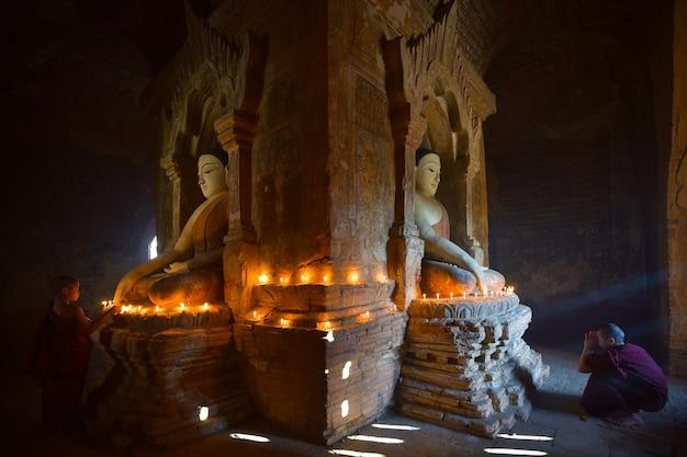 Deux novices allument une bougie et prient dans la pagode bagan au myanmar. Photo Premium