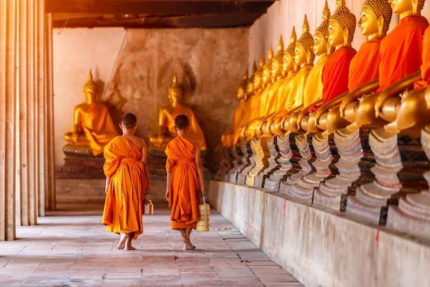 Deux novices marchant reviennent et parlent dans un vieux temple au coucher du soleil, province d'ayutthaya, thaïlande Photo Premium
