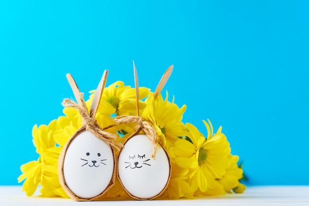Deux oeufs avec des faces de dessin avec des fleurs jaunes sur fond bleu Photo Premium