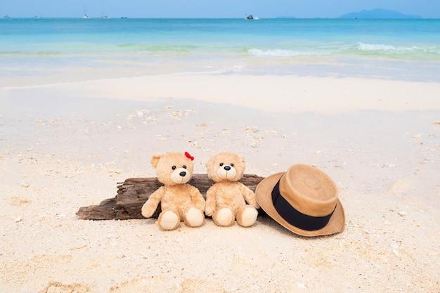 Deux ours en peluche assis sur le bois avec vue sur la mer Photo Premium