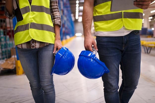 Deux Ouvriers Méconnaissables En Combinaison Réfléchissante Marchant Dans L'entrepôt Et Tenant Un Casque De Protection Bleu Photo gratuit