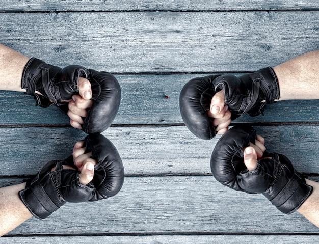 Deux paires de mains humaines dans des gants de boxe en cuir noir se faisant face Photo Premium