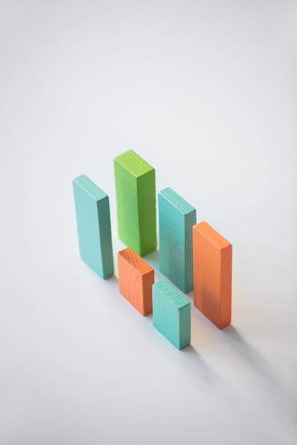 Deux Parallèles De Briques En Bois Plat Bleu, Orange Et Vert Formant Des Graphiques Financiers Isolément Sur Fond Blanc Photo Premium