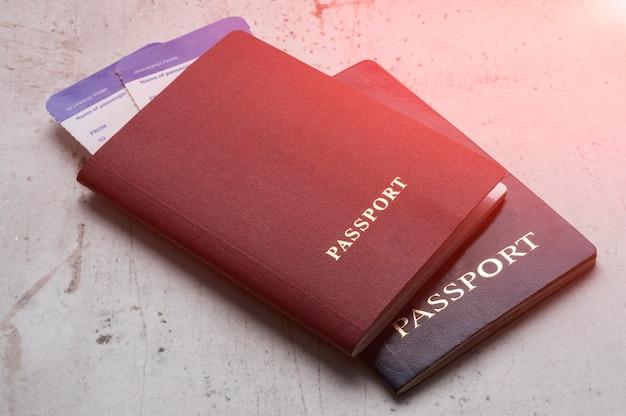 Deux passeports de voyageurs rouge et bleu avec des cartes d'embarquement pour l'avion. Photo Premium