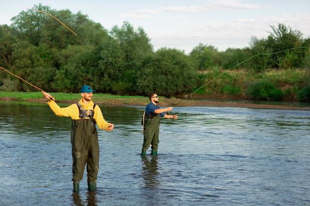 Deux pêcheurs se tiennent dans la rivière vêtus de bottes de caoutchouc Photo Premium
