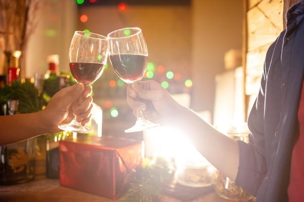 Deux Personnes Célèbrent En Buvant Du Vin. à La Période De Noël Photo Premium