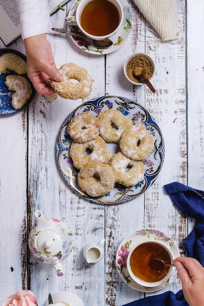 Deux Personnes Prenant Le Thé Et Des Pâtisseries Dans Une Table En Bois Blanc Photo Premium