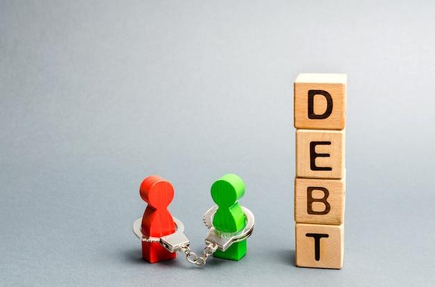 Deux personnes sont liées par des menottes. dette. Photo Premium