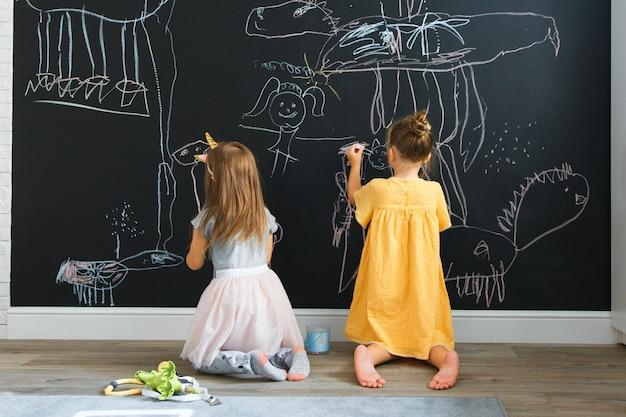 Deux petites filles caucasiennes dessiner sur le mur avec tableau Photo Premium