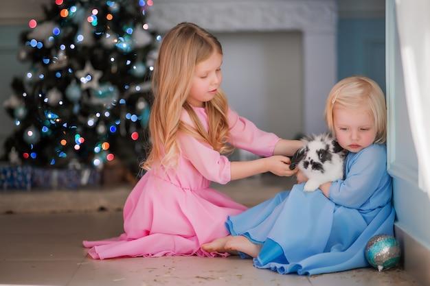 Deux Petites Filles à Côté De L'arbre De Noël Photo Premium