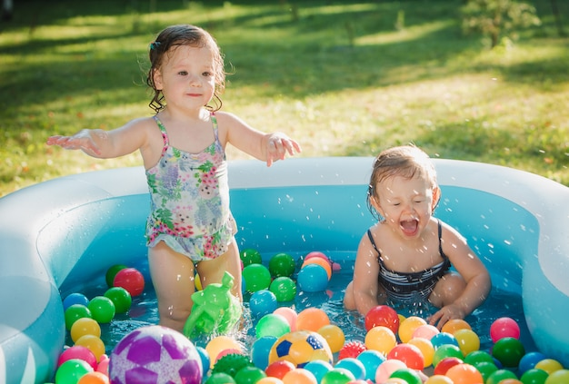 Les Deux Petites Filles Jouant Avec Des Jouets Dans La Piscine Gonflable Dans La Journée Ensoleillée D'été Photo gratuit