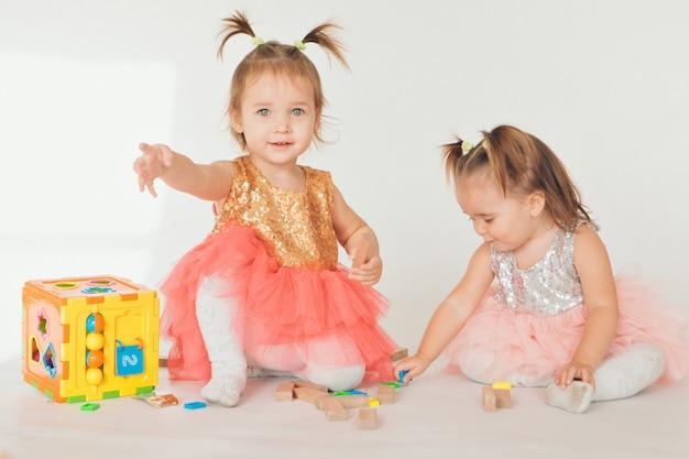 Deux petites filles jouant sur le sol sur un fond blanc Photo Premium