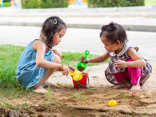 Deux Petites Filles Jouent Au Sable Dans Le Parc. Photo Premium