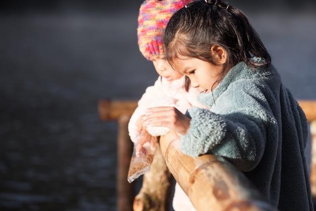 Deux Petites Filles Mignonnes Asiatiques S'amuser à Nourrir Et Donner De La Nourriture Pour Pêcher Dans Le Lac Photo Premium