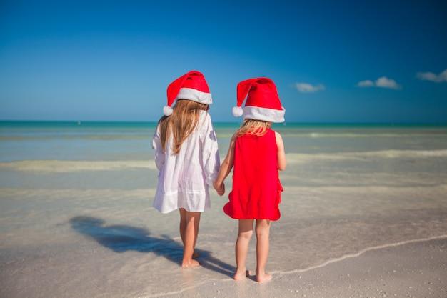 Deux petites filles mignonnes portant des chapeaux de noël s'amusent sur la plage exotique Photo Premium