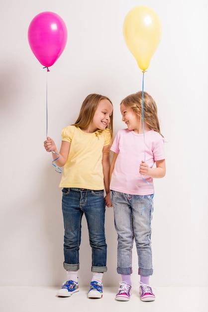 Deux petites filles mignonnes tenant des ballons Photo Premium