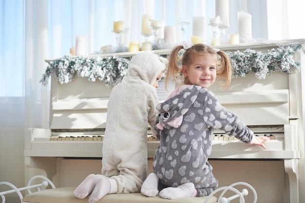 Deux Petites Filles En Pyjama Au Piano Le Jour De Noël Photo Premium