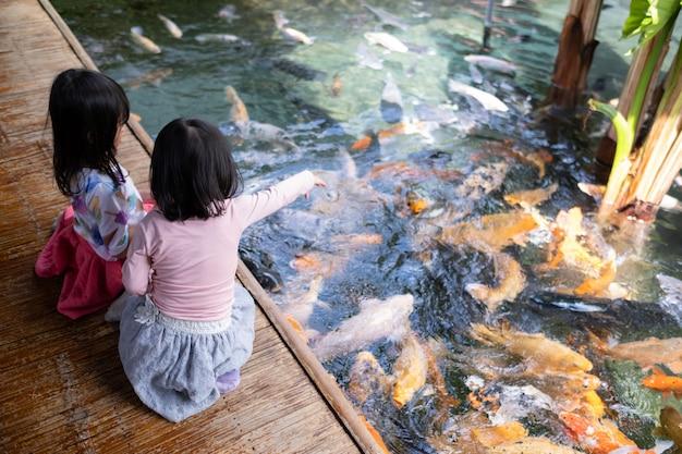 Deux Petites Filles S'amusant à Nourrir Les Poissons Koi Photo Premium