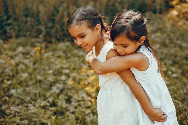 Deux petites soeurs dans un parc d'été Photo gratuit