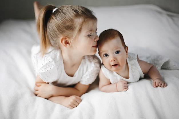 Deux Petites Sœurs Sont Allongées Sur Le Ventre, Vêtues De Jolies Robes Blanches Photo gratuit