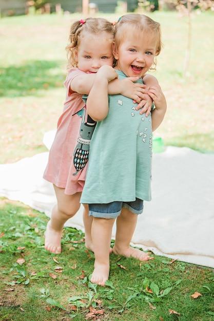 Les Deux Petits Bébés Girsl Jouant Contre L'herbe Verte Dans Le Parc Photo gratuit