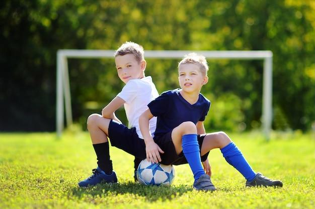 Deux petits frères s'amusant à jouer à un match de football par une journée d'été ensoleillée Photo Premium