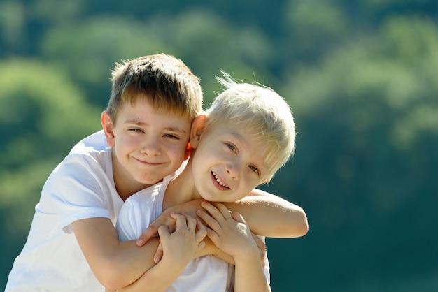 Deux petits garçons s'embrassent dehors. concept d'amitié et de fraternité Photo Premium