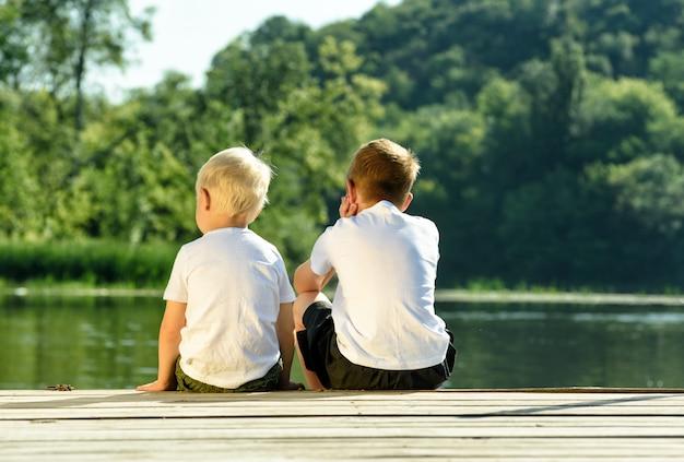 Deux petits garçons sont assis sur la jetée au bord de la rivière. d'amitié et de fraternité. vue arrière Photo Premium