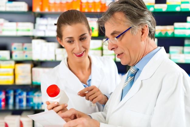 Deux pharmaciens avec des produits pharmaceutiques en train de se consulter dans une pharmacie Photo Premium