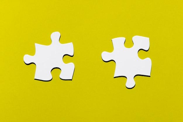 Deux pièces de puzzle blanches sur fond jaune Photo gratuit