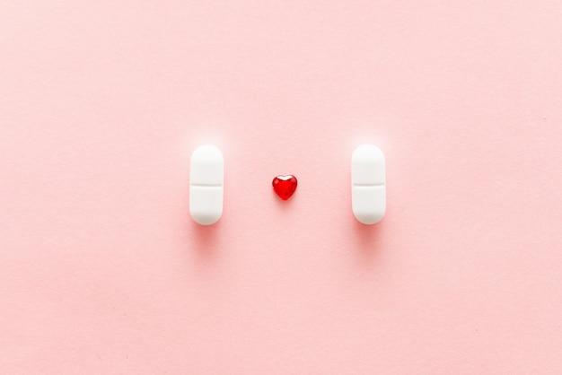 Deux pilules blanches sur fond rose avec forme de coeur rouge, médicaments cardiaques ou concept de guérison féminine Photo Premium