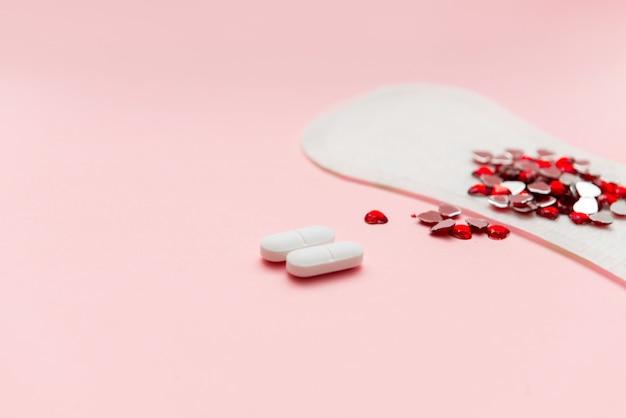 Deux pilules et tampon de menstruation avec un cœur rouge dessus, concept de contraception anti-douleur Photo Premium