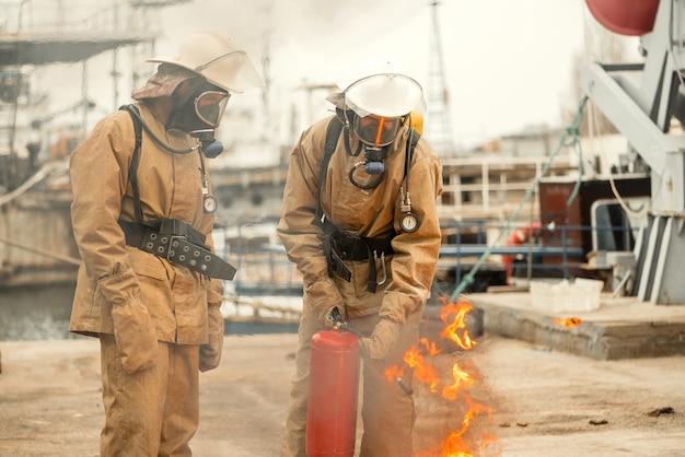 Deux pompiers portant des masques et du matériel lors d'une formation sur la façon d'éteindre l'incendie Photo Premium