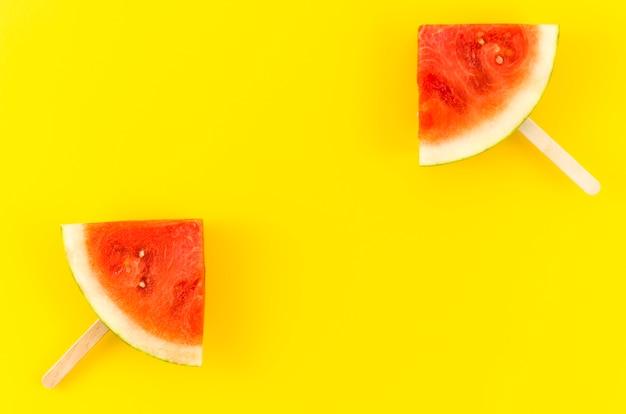 Deux, popsicles tranche pastèque, sur, jaune, table Photo gratuit