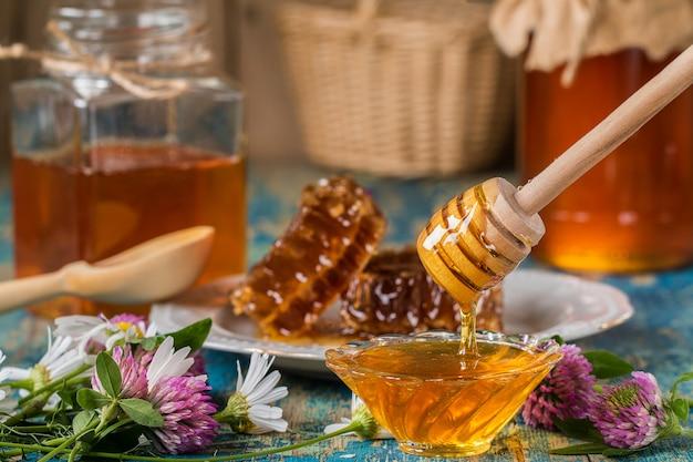 Deux pots de miel avec nid d'abeille sur une table en bois avec des fleurs Photo Premium