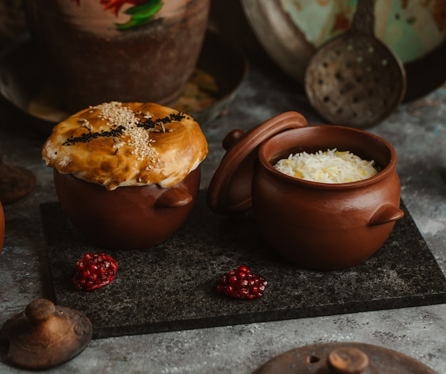 Deux pots de poterie avec une tarte et du riz à l'intérieur. Photo gratuit