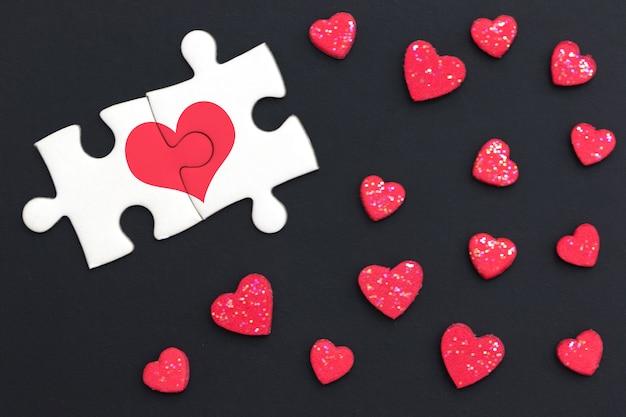 Deux puzzles ont peint coeur rouge et ont continué sur fond noir avec beaucoup de coeur rouge. Photo Premium