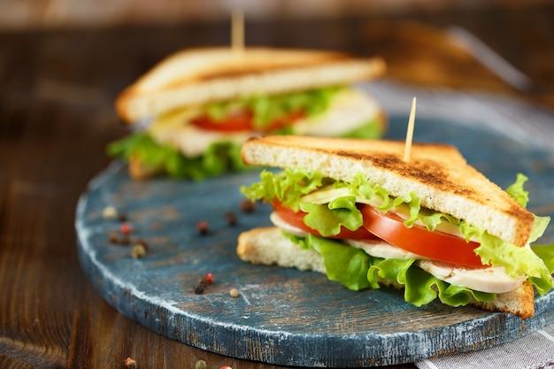 Deux savoureux sandwich au poulet, tomates, laitue, fromage sur une plaque de bois sur un fond sombre Photo Premium