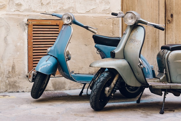 Deux scooters vintages stationnés sur la rue Photo gratuit