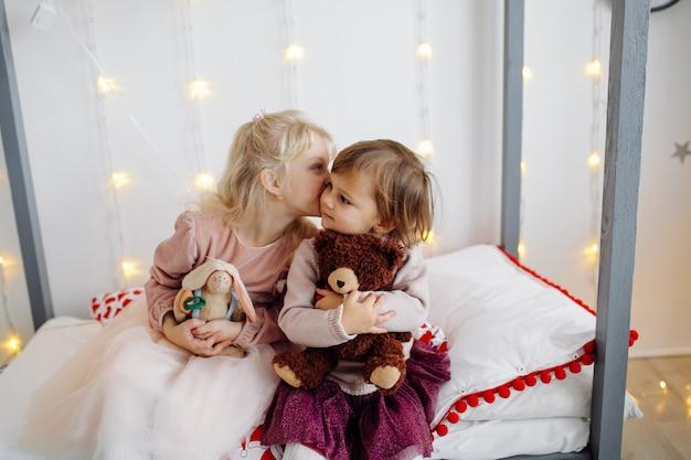 Deux soeur posant pour une photo pendant la prise de photos de famille Photo gratuit